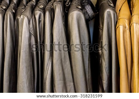 Collection of leather jackets on hangers in the shop - stock photo