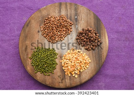 Collection of Lentils, beans various colors on wooden circle shape base/ table  purple background, top view Kerala, India. legumes chickpeas, green lentils, green mung, pulse, rice and dal/ dhal - stock photo