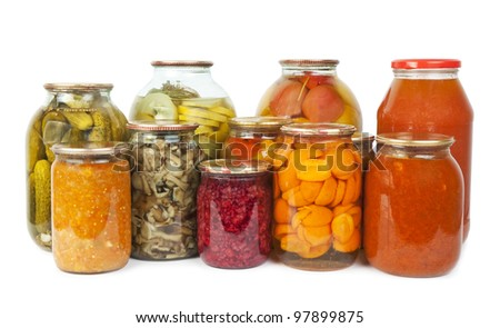 Collection of many glass bottles with preserved food on white background