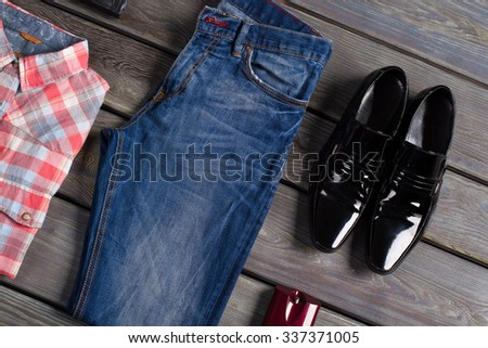 Collection of men's clothing and accessories on a wooden background. - stock photo