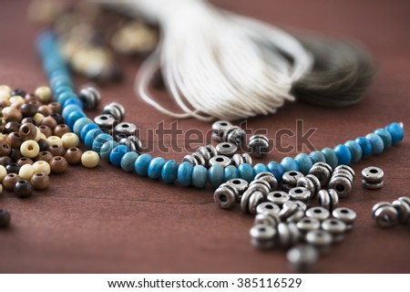 Collection of metal, wooden and turquoise beads with cord for jewelry making.