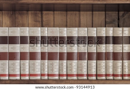 Collection of old books. Could be encyclopedias, concordances, series etc. Sitting on a beautiful wooden book shelf. - stock photo