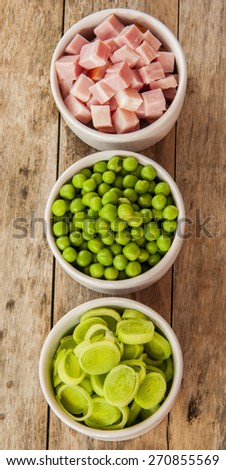 collection of peas,leek and bacon in small withe bowls on wood - stock photo