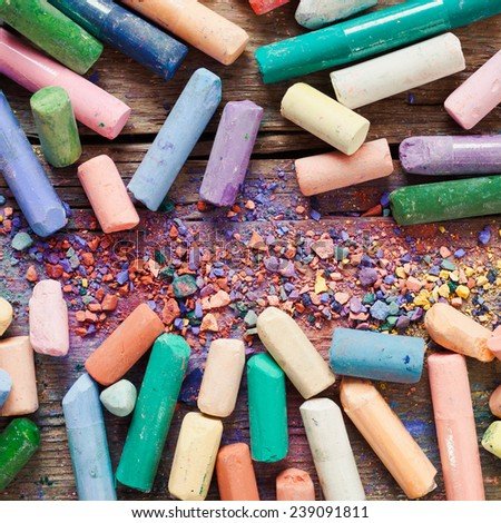 Collection of rainbow colored artistic pastel crayons with pigment dust on old wooden desk. - stock photo