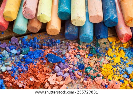 Collection of rainbow colored pastel crayons with crushed chalk closeup on desk. . - stock photo