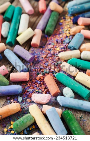 Collection of rainbow colored pastel crayons with pigment dust on old wooden desk. - stock photo