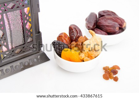 Collection of Ramadan dried fruits - Dates , Figs, Raisin, Qrasia; Apricots on a table with lantern for happy breakfast in Ramadan - stock photo