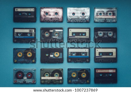 Collection Of Retro Audio Tapes On Blue Background, Top View. Retro Technolody Music Concept