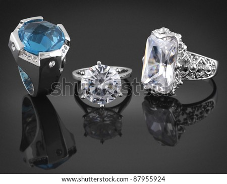 Collection of rings with diamonds on black background - stock photo