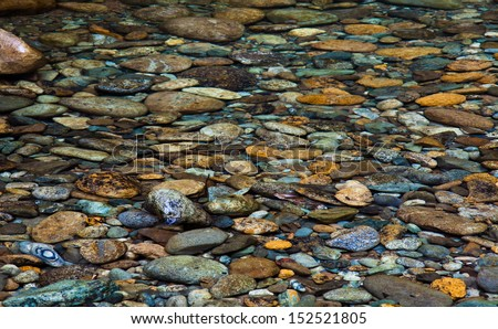 Collection of river rock in a stream - stock photo