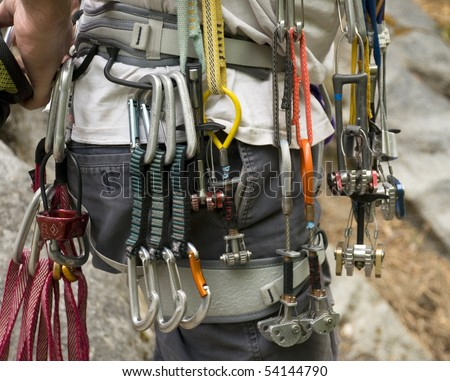 Collection of rock climbing gear attached to a climber's harness - stock photo