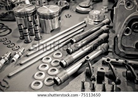 collection of sepia toned precision auto engine parts laid out in a workshop - stock photo