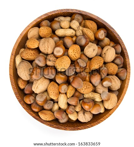 collection of shelled nuts in a wooden bowl isolated on white - stock photo