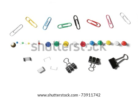 Collection of stationary isolated on white. Including a selection of four types of push pins, paper clips, bulldog clips and staples. Multiple colors - stock photo