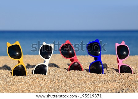 Collection of Sunglasses on the beach - stock photo