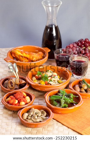 Collection of tapas foods including dates in bacon, butter beans with chorizo, mushrooms, seafood salad, chicken in tomato sauce and pickled olives and red wine. - stock photo
