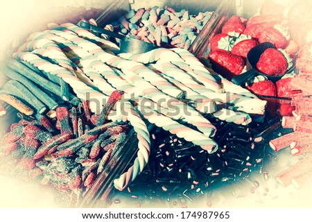Collection of the colorful gummy and marshmellow candies at market. Toned image. Vintage food background. Bleached angles. - stock photo