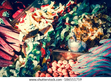 Collection of the colorful gummy and marshmellow candies at market. Toned image. Vintage food background. Shadowed angles. - stock photo