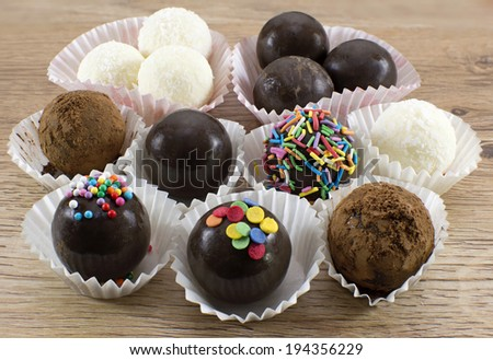 Collection of the decorated chocolate candies in white wrappers - stock photo