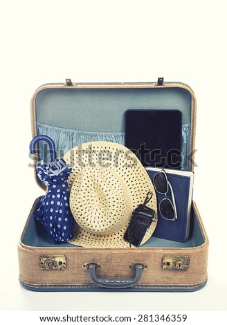 Collection of vacation travel items with a vintage filter in a suitcase - stock photo