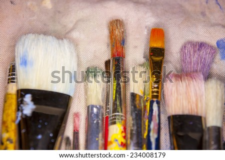 collection of various artists brushes in all sizes on a canvas background - stock photo