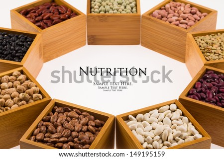 Collection of various beans contained in wood boxes on a white background. - stock photo