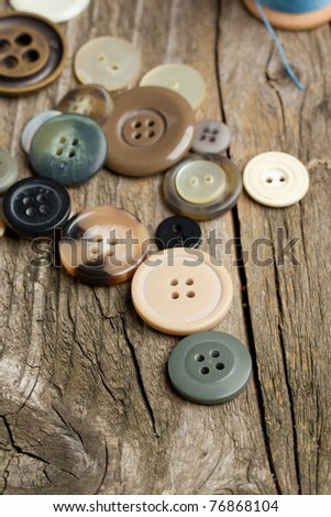 Collection of various buttons on old wooden table - stock photo