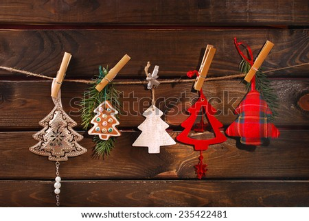 collection of various christmas tree shaped decorations hanging on twine against wooden background - stock photo