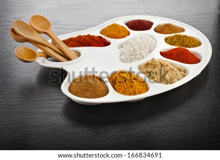 Collection of various colorful spices on a cooking palette with wooden spoon on black wooden surface table - stock photo
