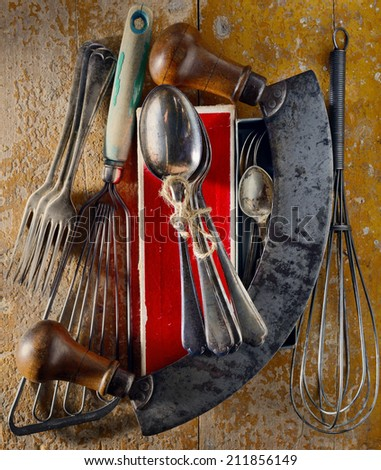 Collection of vintage kitchen utensils and silver spoons found at a flea market arranged on a grunge wooden surface. Directional light.  - stock photo