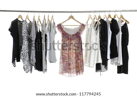 collection of women's clothes hanging on a rack. - stock photo