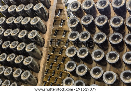 Collection sparkling wines aging in the rack in winery cellar - stock photo