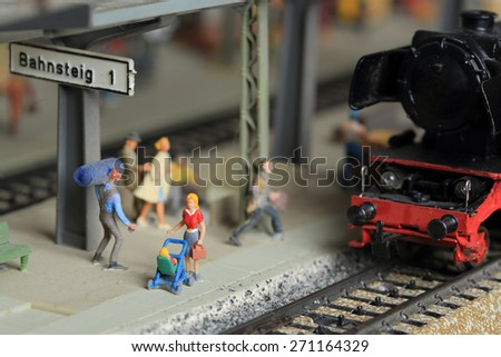 Collector's miniature train at the railway station on track 1. A woman with a baby and stroller is walking on the station platform.  - stock photo