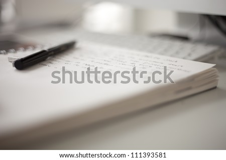 college book with writing on a desk in front of a computer - stock photo
