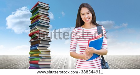 College girl holding books with blurred students in park against stack of books against sky - stock photo