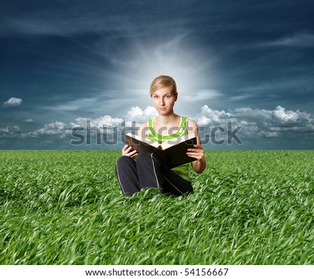college girl reading big book in green grass - stock photo