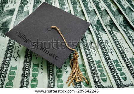College Graduate cap on assorted hundred dollar bills                            - stock photo
