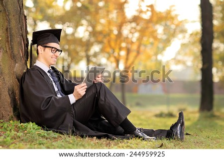 College graduate working on a tablet seated by a tree in park - stock photo