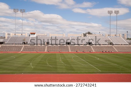 College Level Track Stadium Puffy Clouds Blue Sky - stock photo