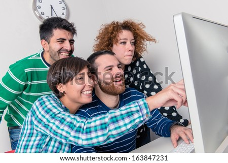 College or university students studying using a computer sitting together at a long table in the classroom reading something together on the monitor - stock photo