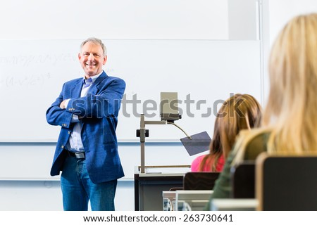 College professor giving lecture in college standing at desk - stock photo