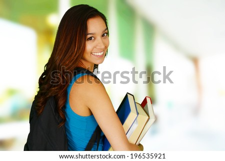 College student carrying her books at school