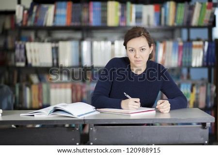 College student doing some homework at the library - stock photo