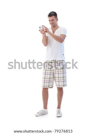 College student dressed for summer taking digital phot, smiling.? - stock photo