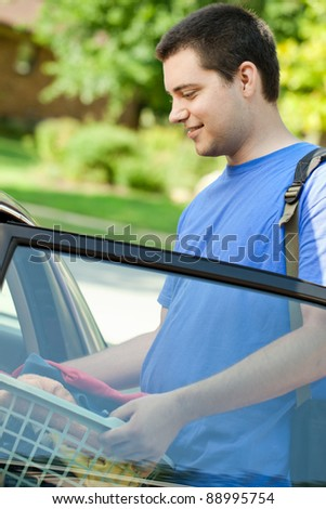 College student getting in the car with laundry basket and backpack - stock photo