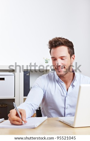 College student learning with computer and taking notes - stock photo