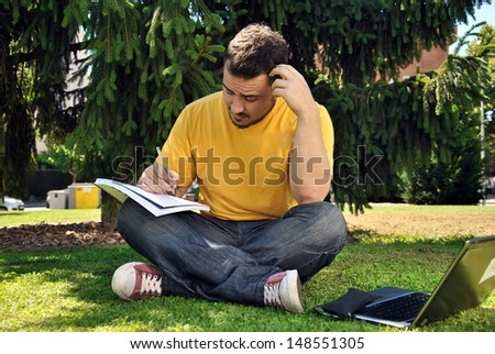 college student lying on the grass in the sun - stock photo