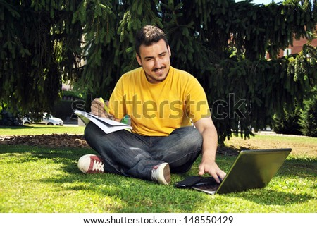 college student lying on the grass in the sun with her computer - stock photo