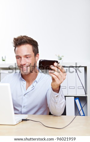 College student making data transfer from cell phone to laptop computer - stock photo