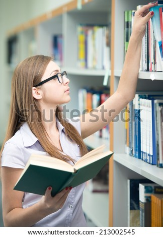 College student on university campus picking book from shelf - stock photo